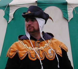 C14th Black Silk Cap, trimmed with Gold Braid and centre front Escutcheon, with a Pheasant feather
